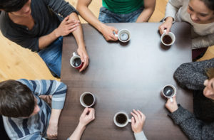 Young adults drinking coffee around a table
