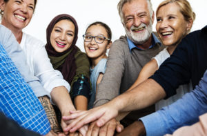 Diverse community putting hands on top of each other
